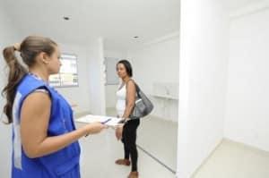 Doméstica Cleuza da Silva conversa com funcionária e obtém informações sobre o sorteio dos apartamentos.