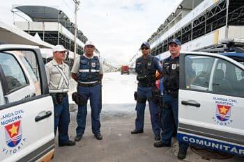 Guardas Civis Municipais em pé entre duas viaturas