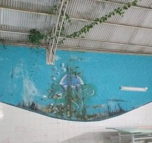AS áreas comuns da escola estão com paredes mofadas, piso irregular e com canos e fios expostos. Foto: colaboradora